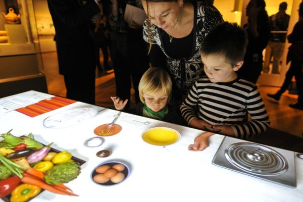 "At Fernbank Museum of Natural History's exhibit ""Food - Our Global History"" visitors can explore an interactive cooking table, where they ""make"" famous dishes eaten around the world."