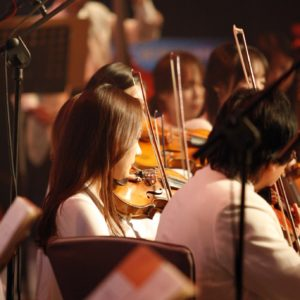 woman plays violin in large orchestra setting