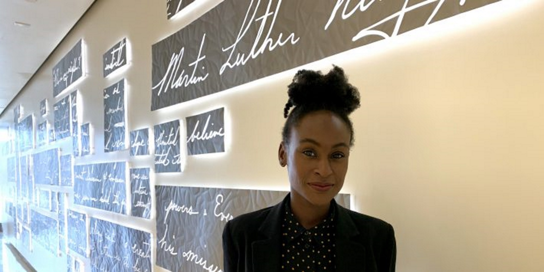 """Lauren Baeza, director of exhibitions at Atlanta's National Center for Civil and Human Rights, stands near the new exhibit """"We Share the Dream"""" in January."""